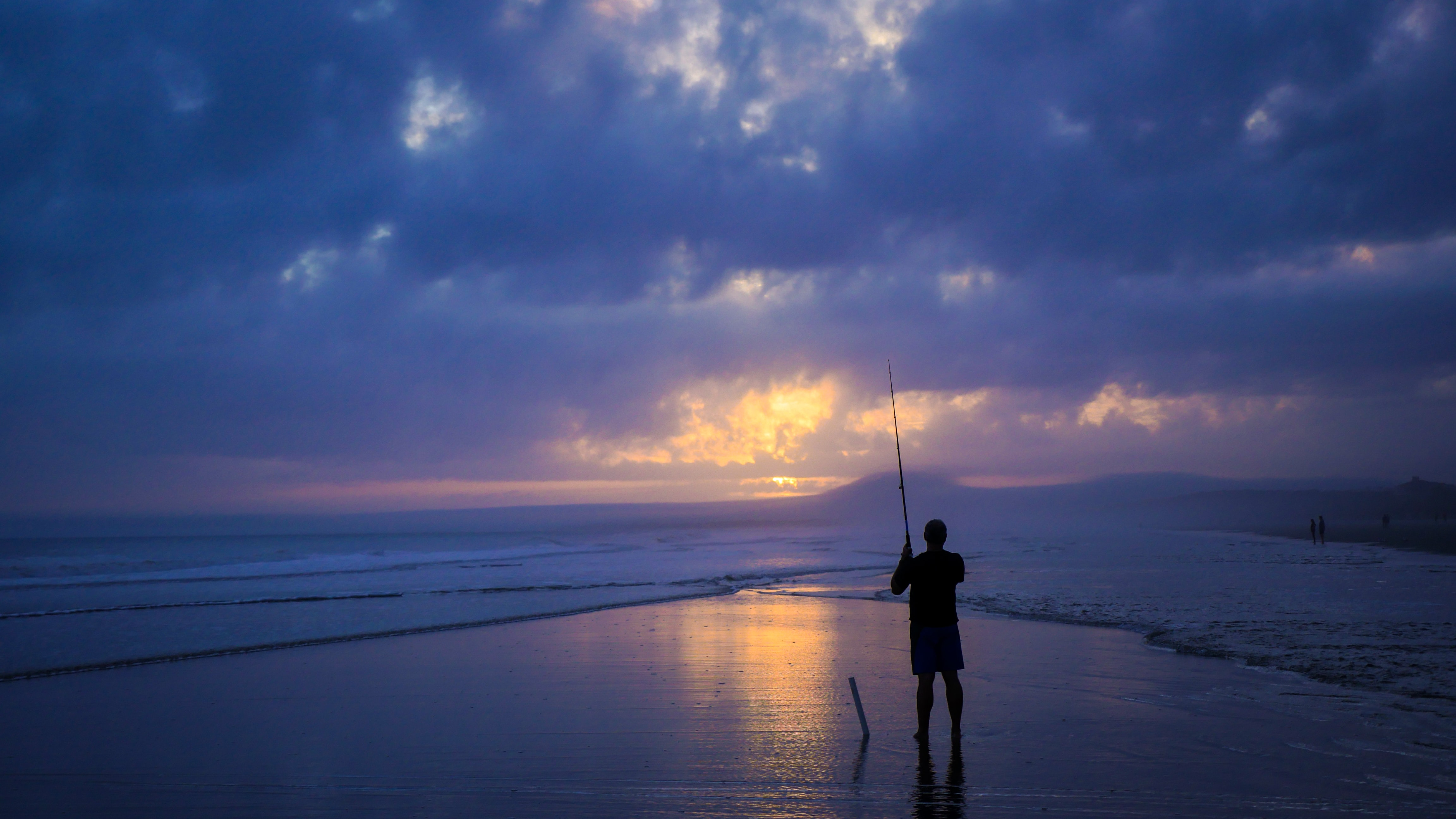 A silhouette of a fisherman fishing on a beach on Kiawah Island in the evening