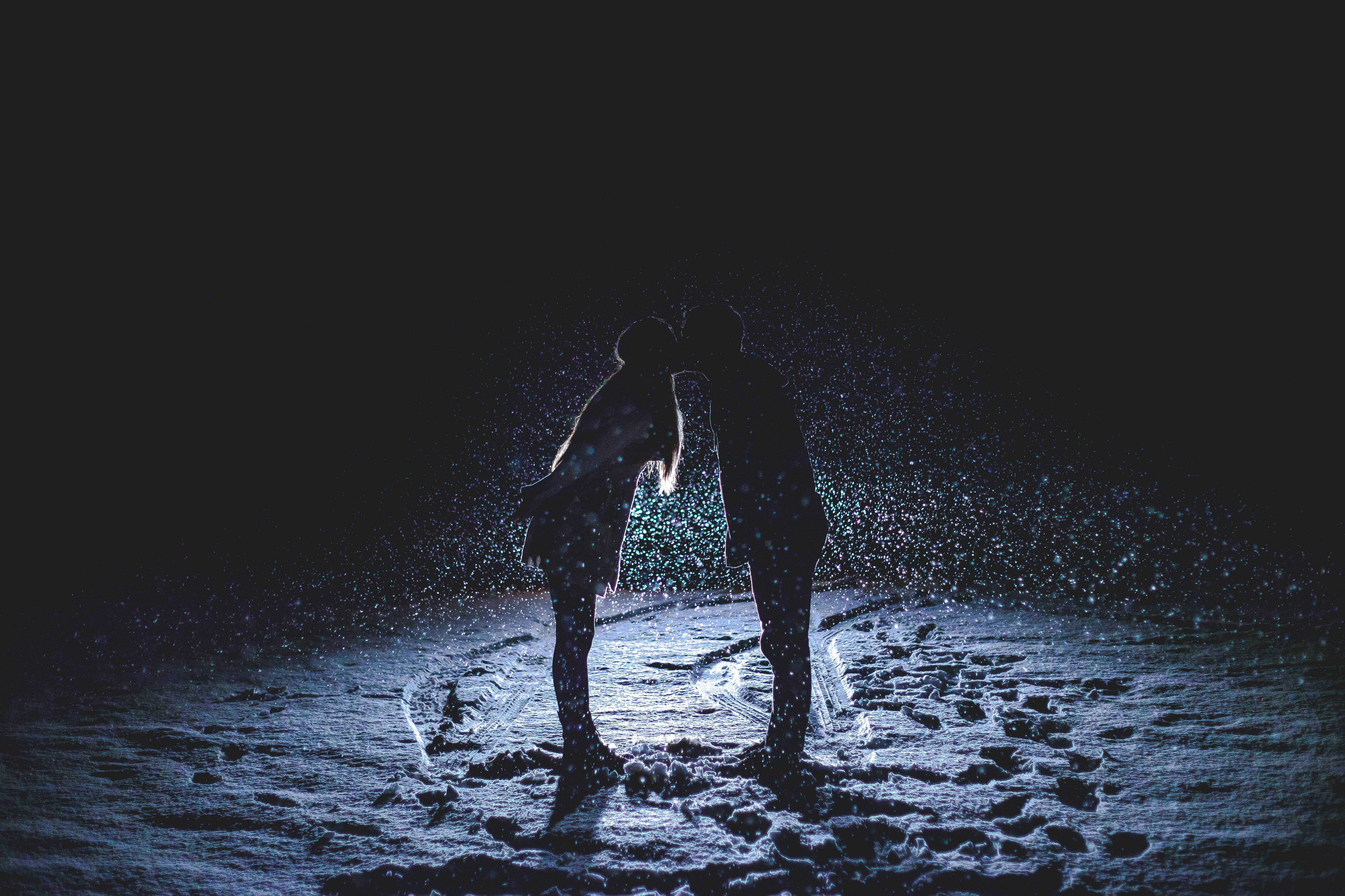 As snow falls around them, a couple kiss backlit at night