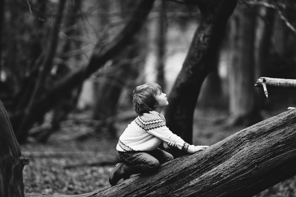 boy climbing fallen tree