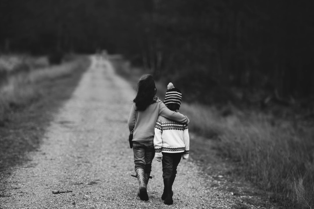 Black and white shot of children in sweaters walking down an unpaved road