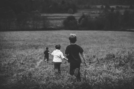 three boys running on field