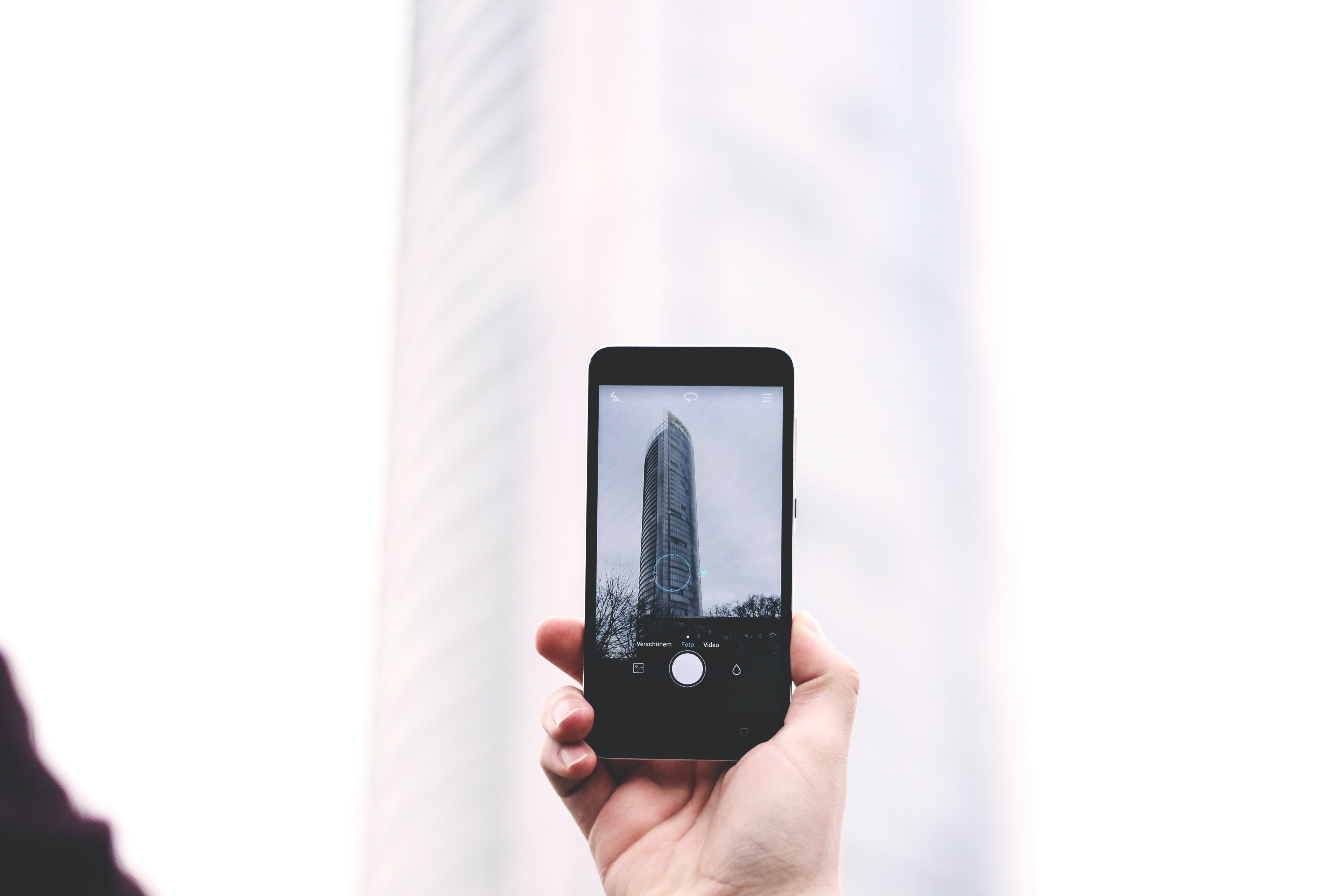 shallow focus photography of person taking picture of glass tower at smartphone