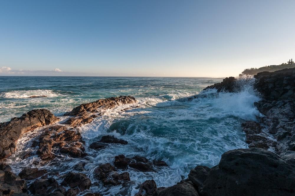 ocean waves hammering rock boulders