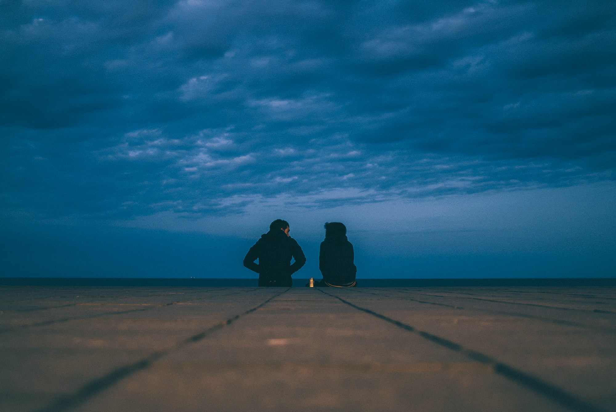 Low angle shot of two people sitting next to each other on a cloudy evening on a wooden floor.