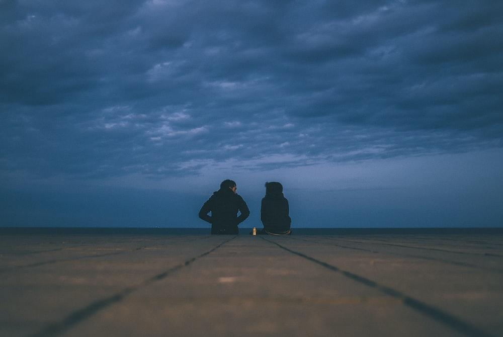 two people wearing black jackets sitting on floor