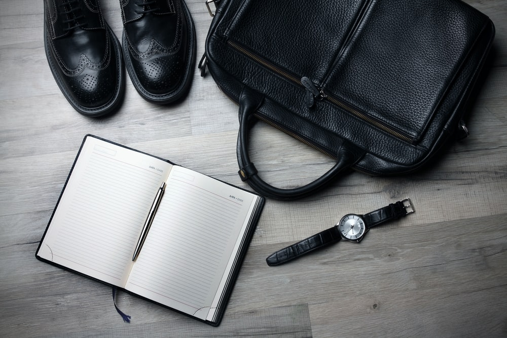 An overhead shot of a leather bag, a pair of leather shoes and a watch next to an open notebook