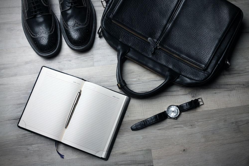 white notebook near black bag