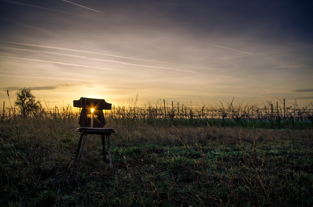 silhouette of a person sitting on a chair during sunset