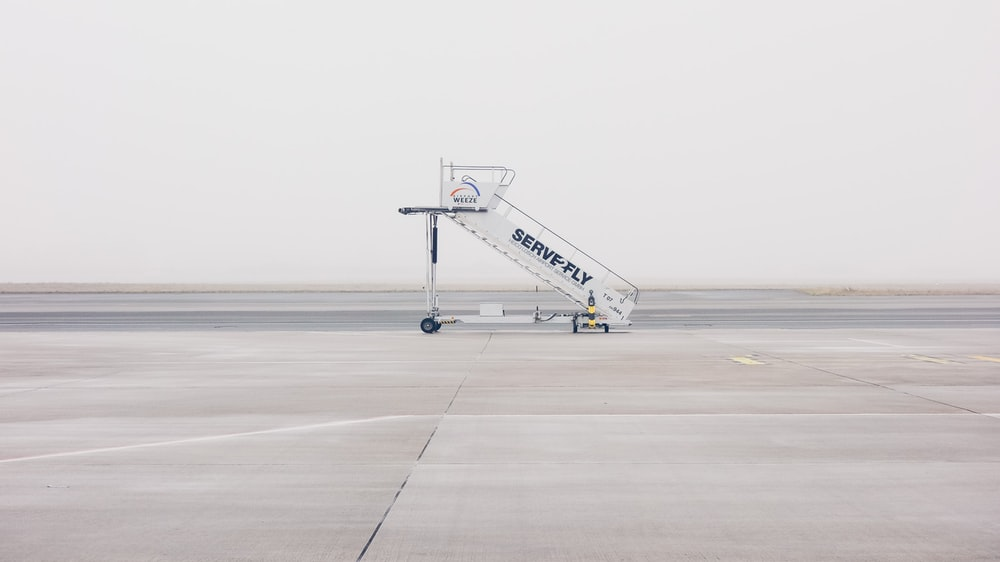 white airliner stairs on runway