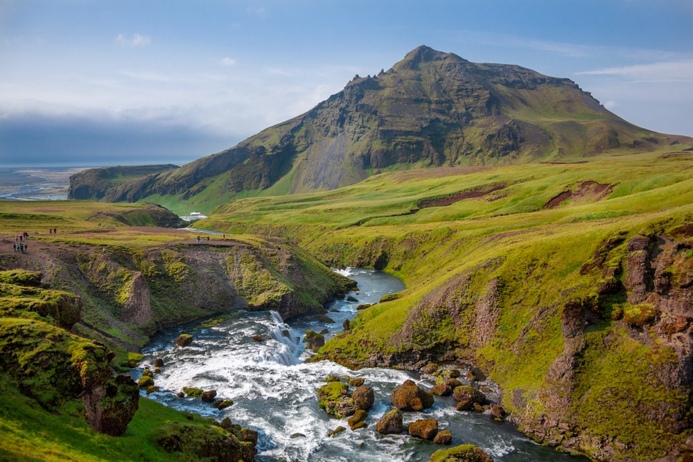 photo of river and green grass covered moutain