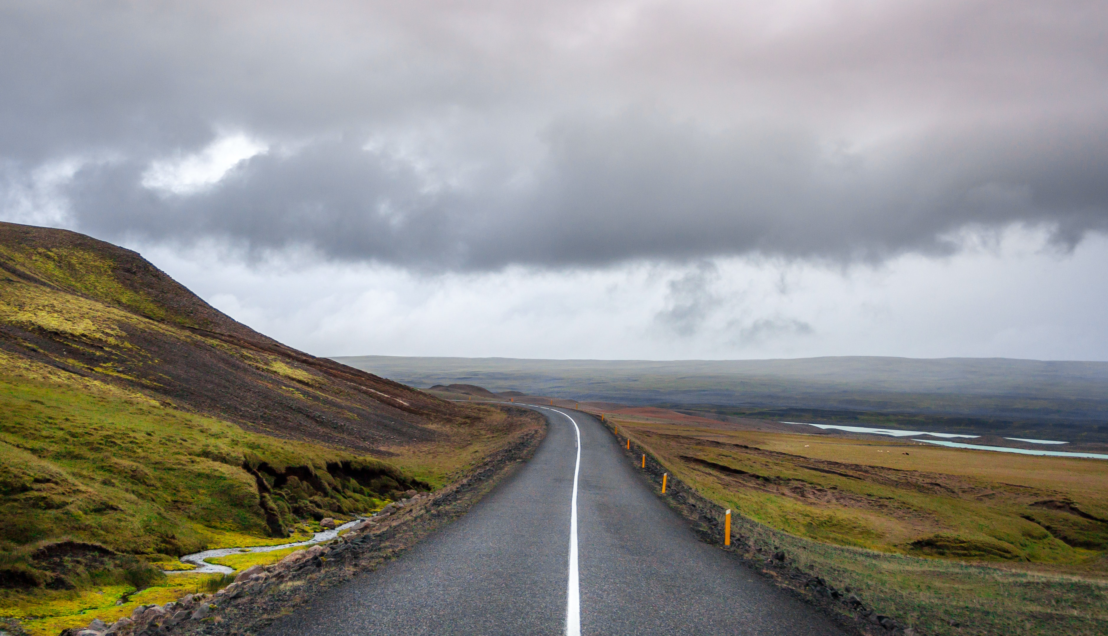 Open road leads through a rural grassy hillside on a cloudy day