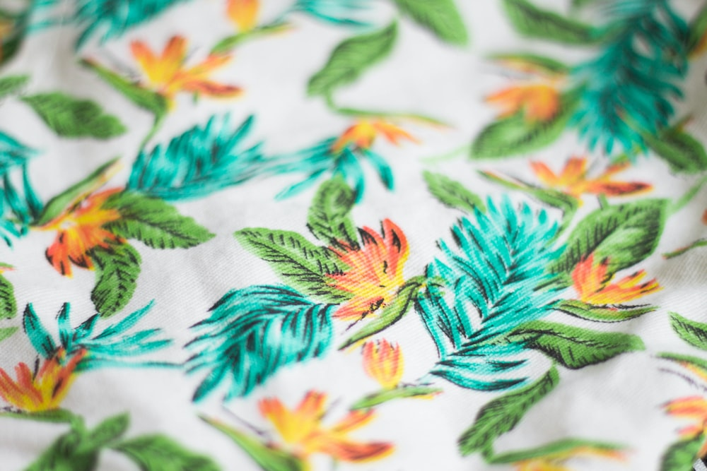 white, green, and teal floral textile