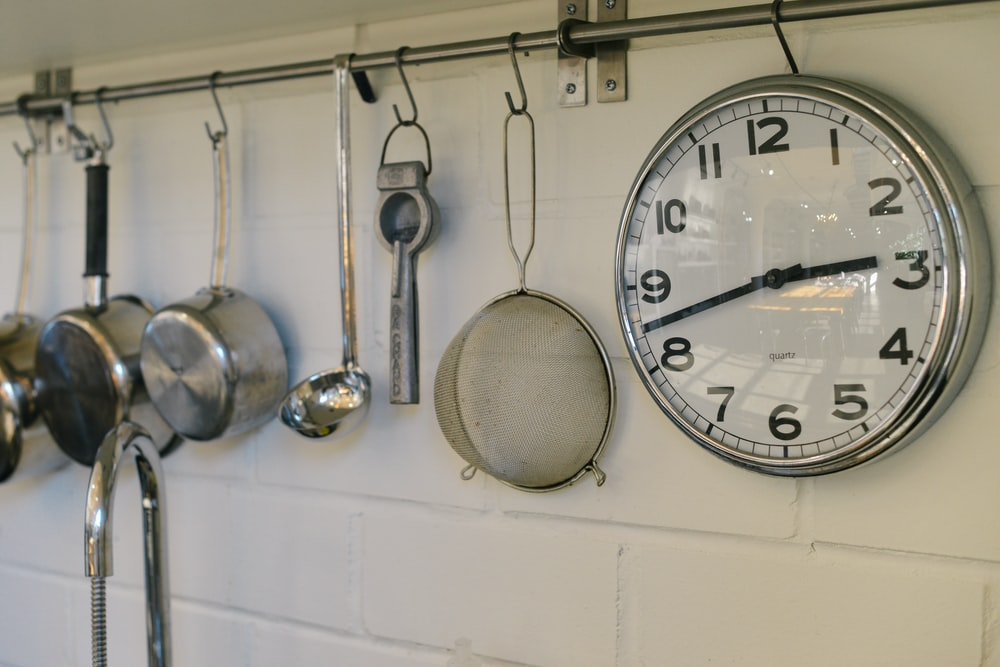 round white and gray stainless steel analog clock displaying 02:43 time near gray stainless steel saucepans hanging on wall