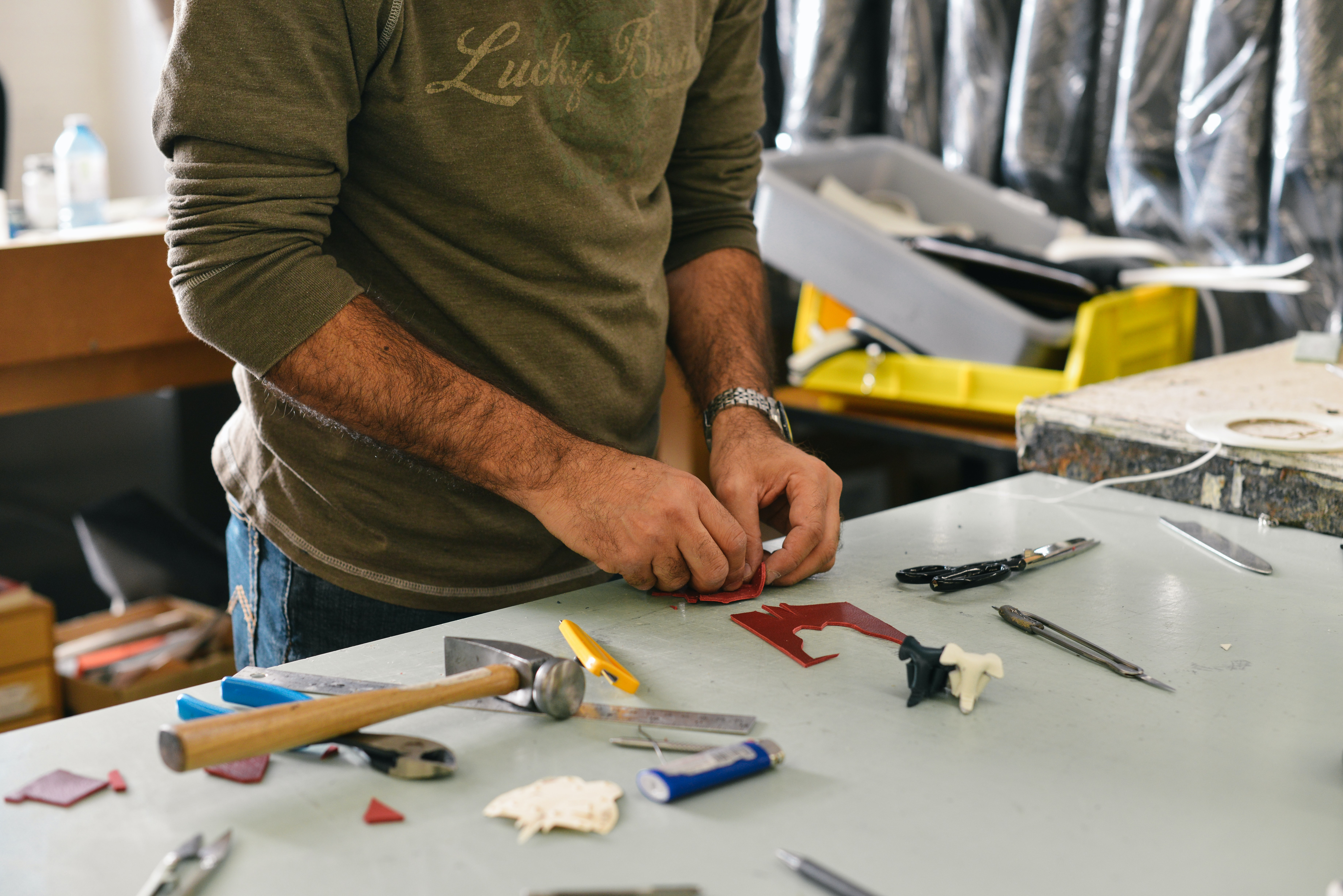 A man working on a craft project at a table with tools and pieces of plastic