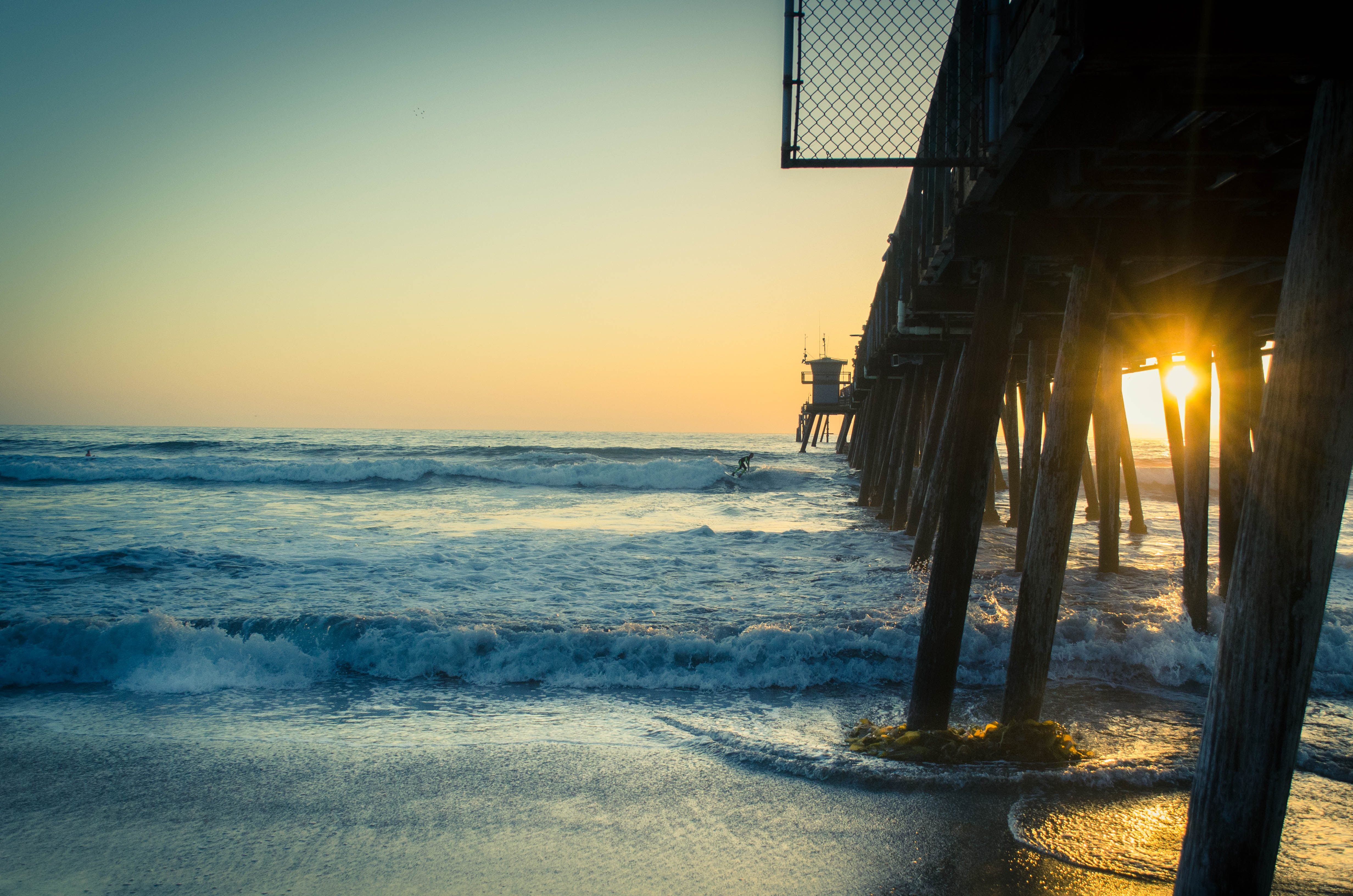 View of the wooden pier pillars blocking the sunset at Imperial Beach