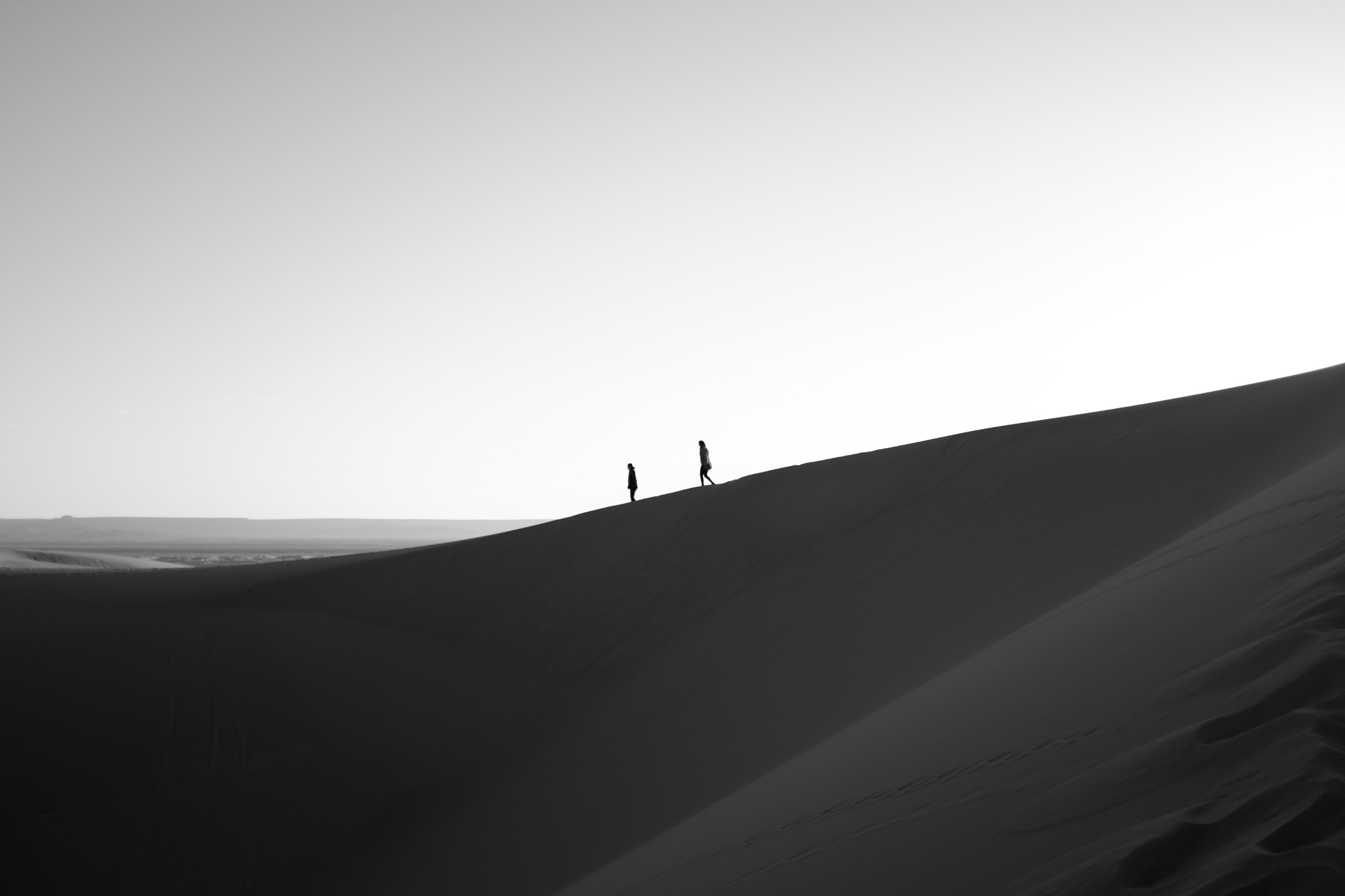Black and white image of two people walking across sand dunes in the distance