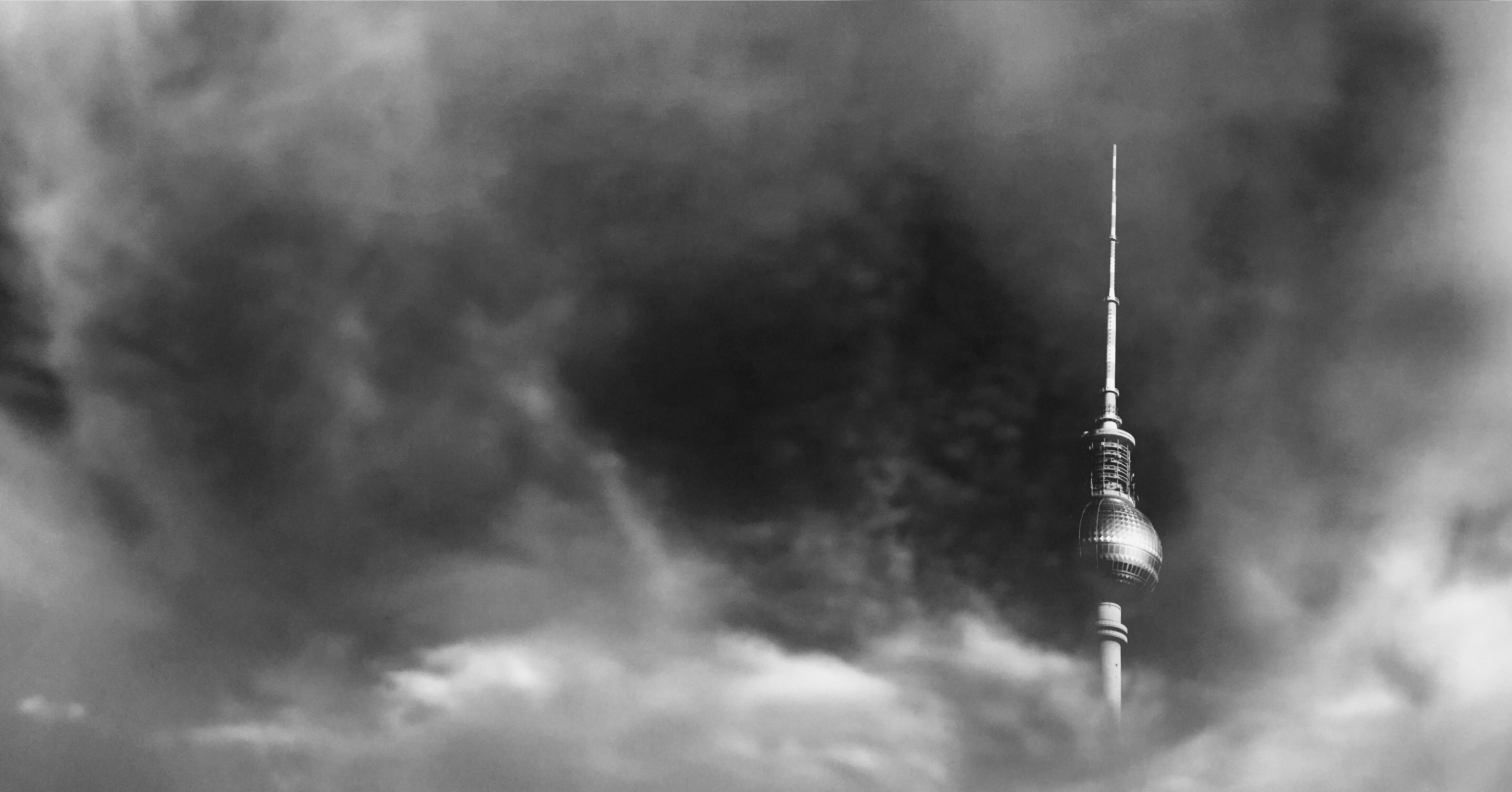 The Fernsehturm tower in Berlin shrouded in gray clouds