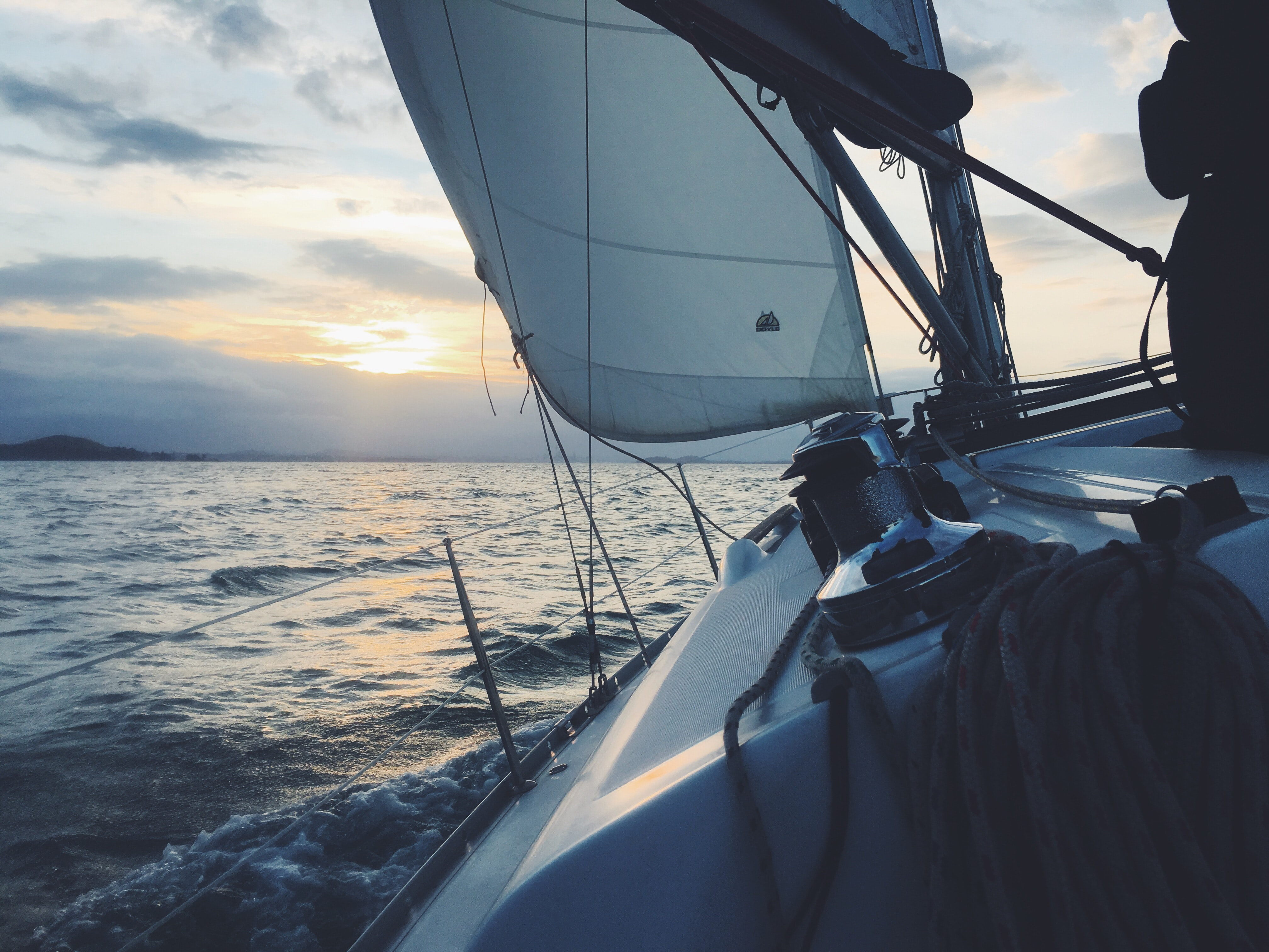 View from a sailing yacht on the choppy sea around at sunset