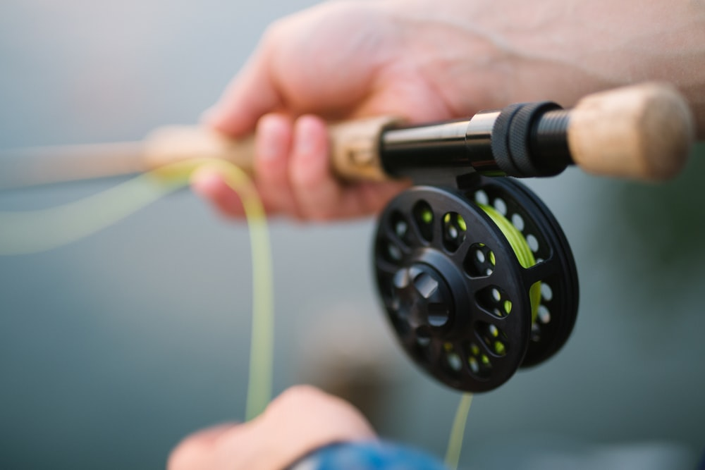 person holding black and brown fishing rod