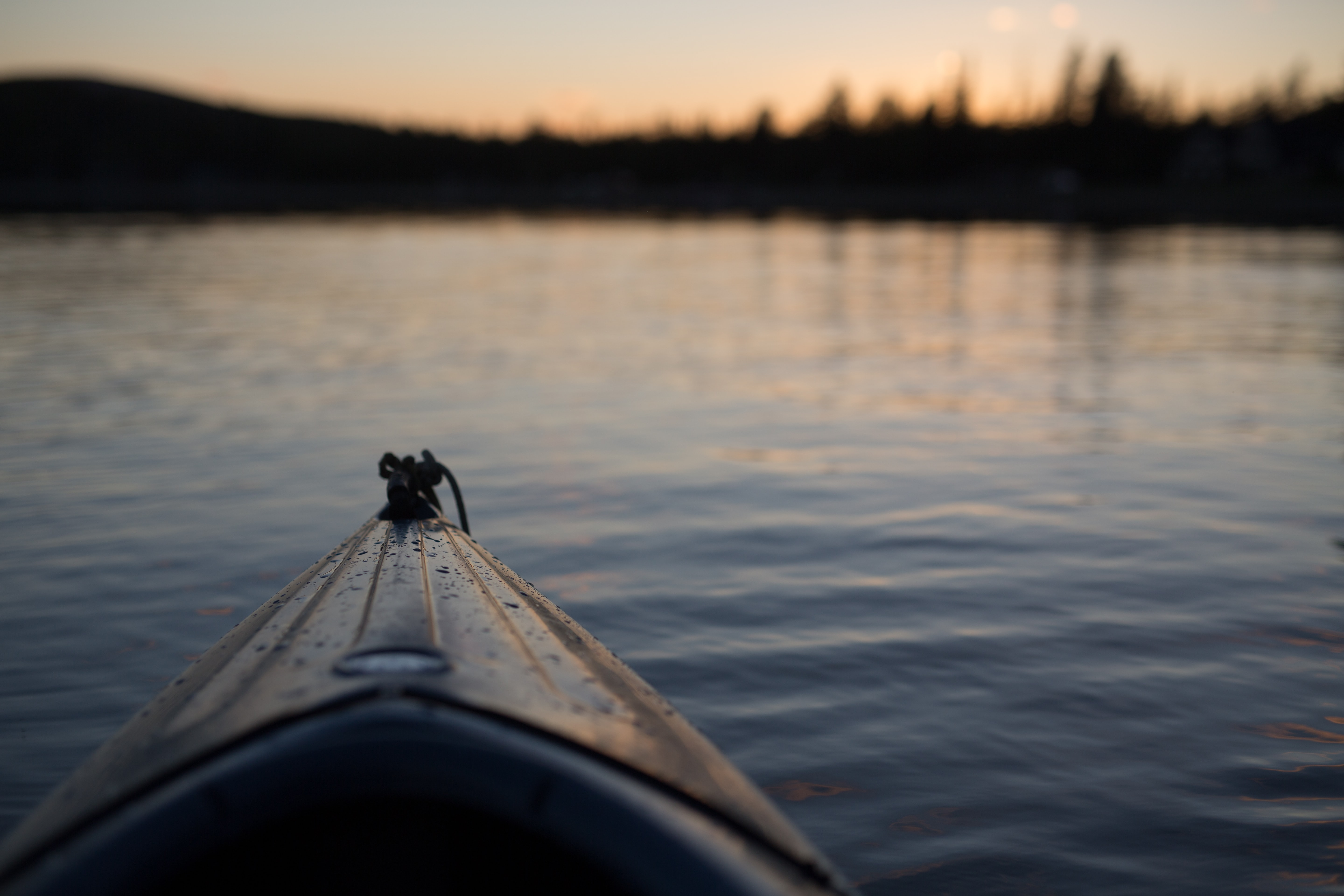 The front of a canoe floating in the river covered with water droplets at sunset or sunrise