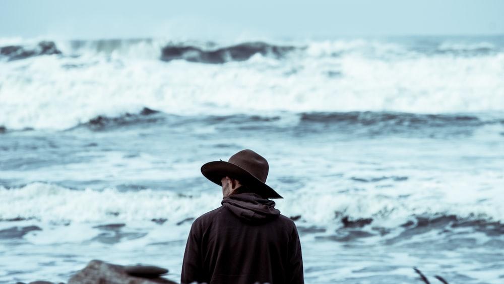 man wearing brown hat standing in front of ocean