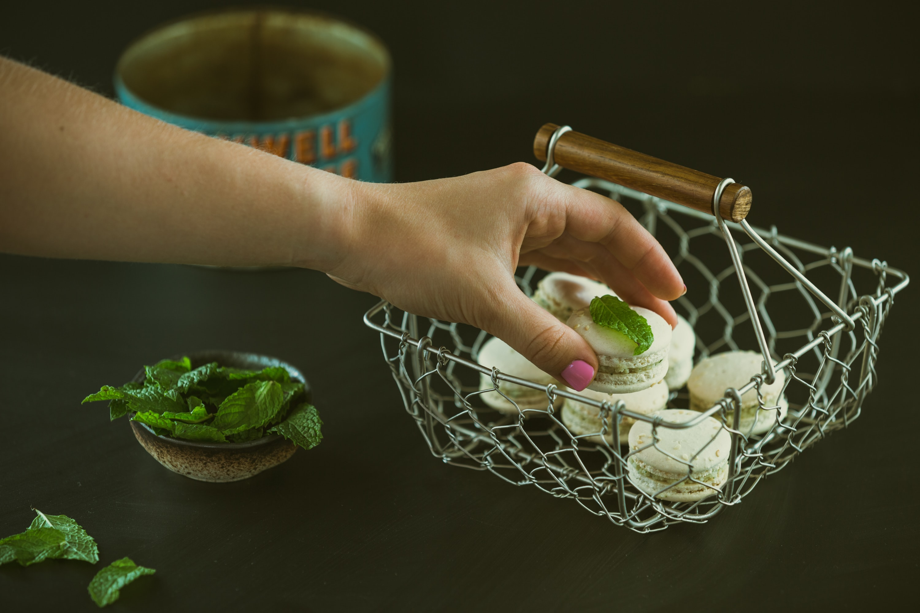 Hand stacks fresh macarons with mint in a basket