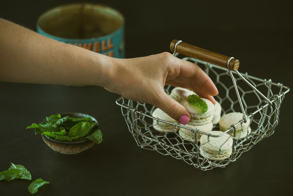 person holding round cookie near green leaf vegetable