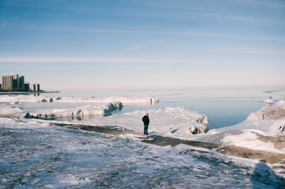 man stands between snowfield near body of water