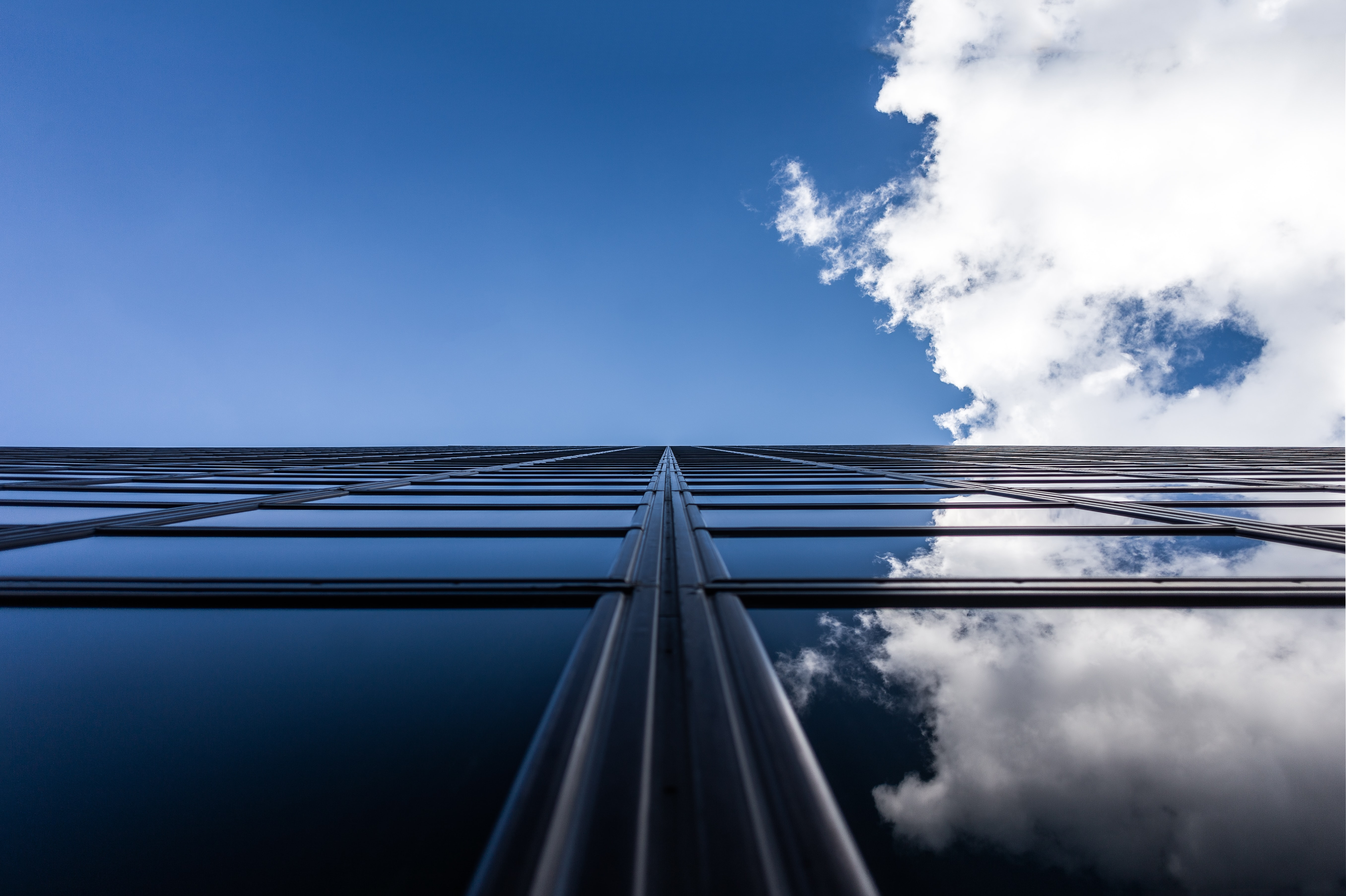 Clouds and blue sky reflected in windows of a modern building
