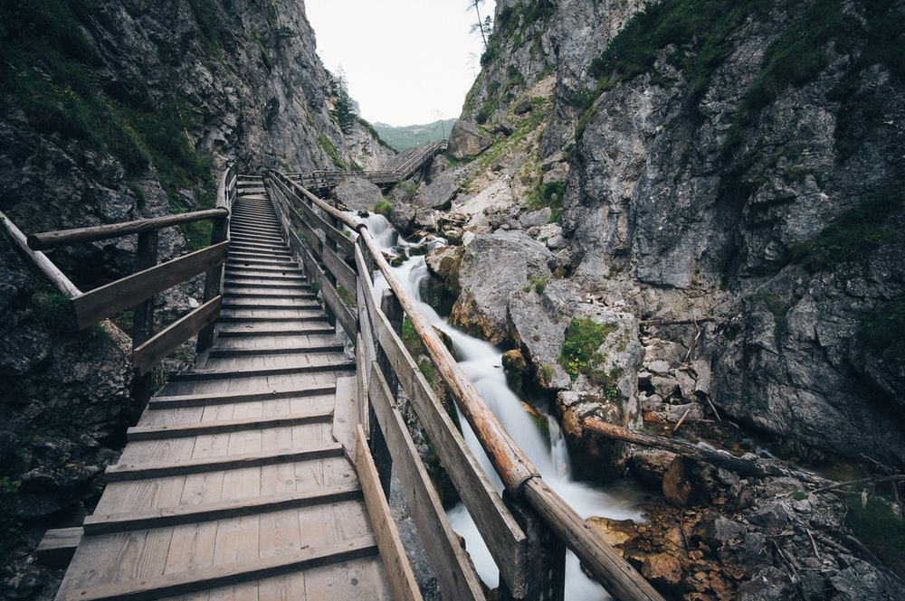 brown wooden bridge in the middle of two mountain