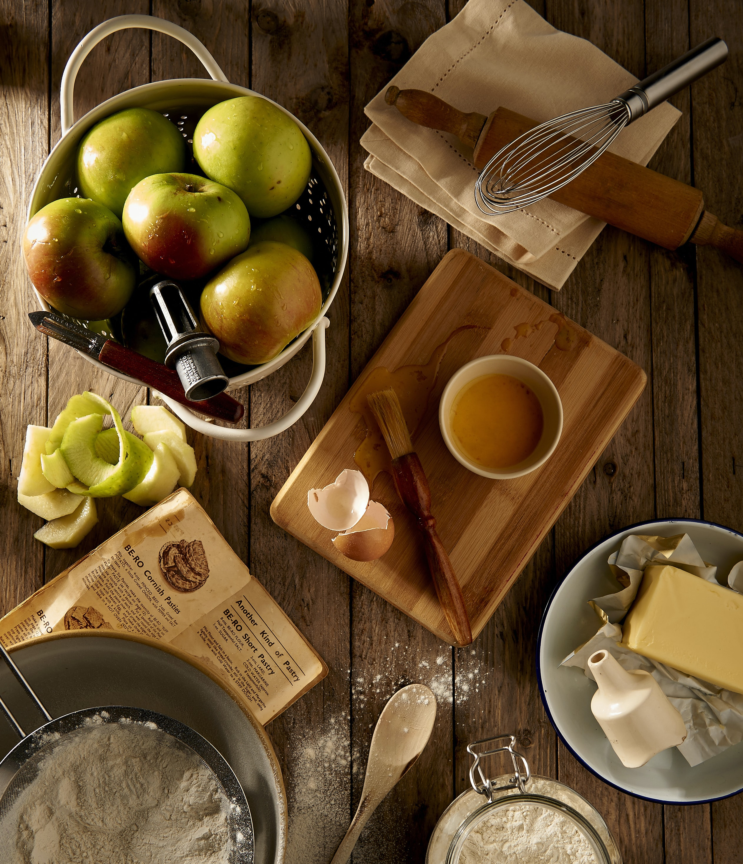 Flat lay of apples, butter, flour, and ingredients for an apple pie