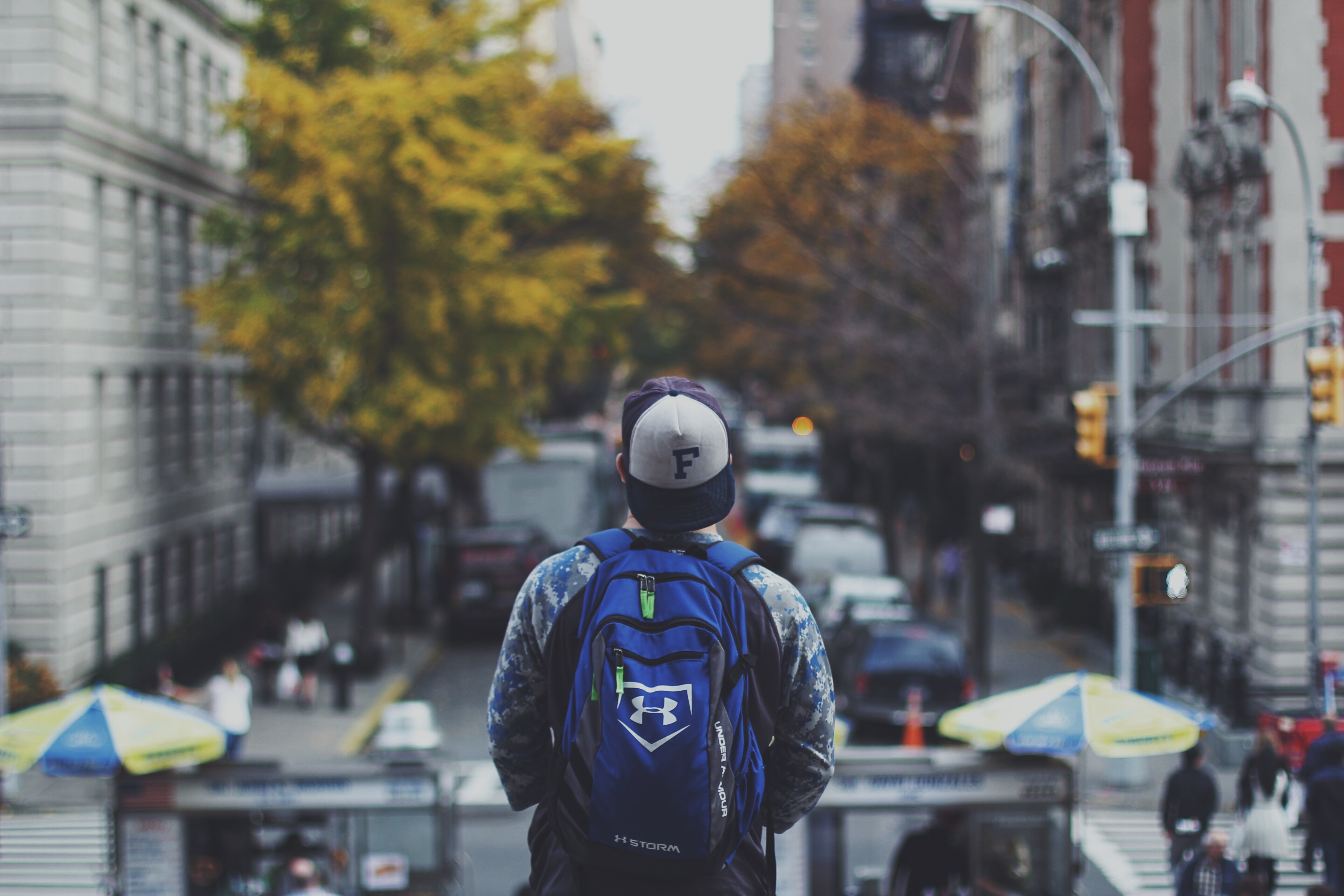 A man in a cap and a backpack looking at a busy street in New York.