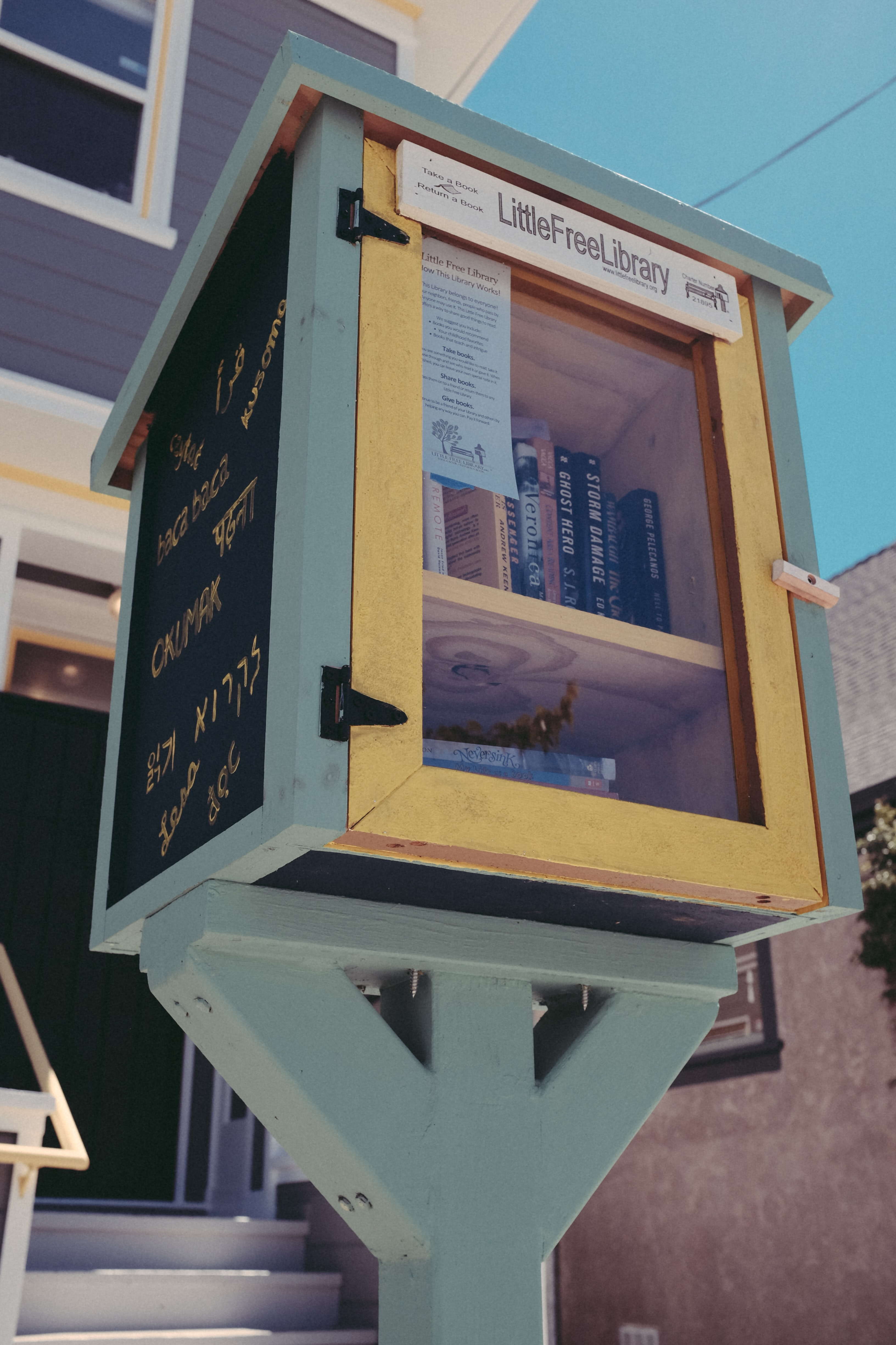 Little Free Library stand with clear door and library books inside and writing on exterior