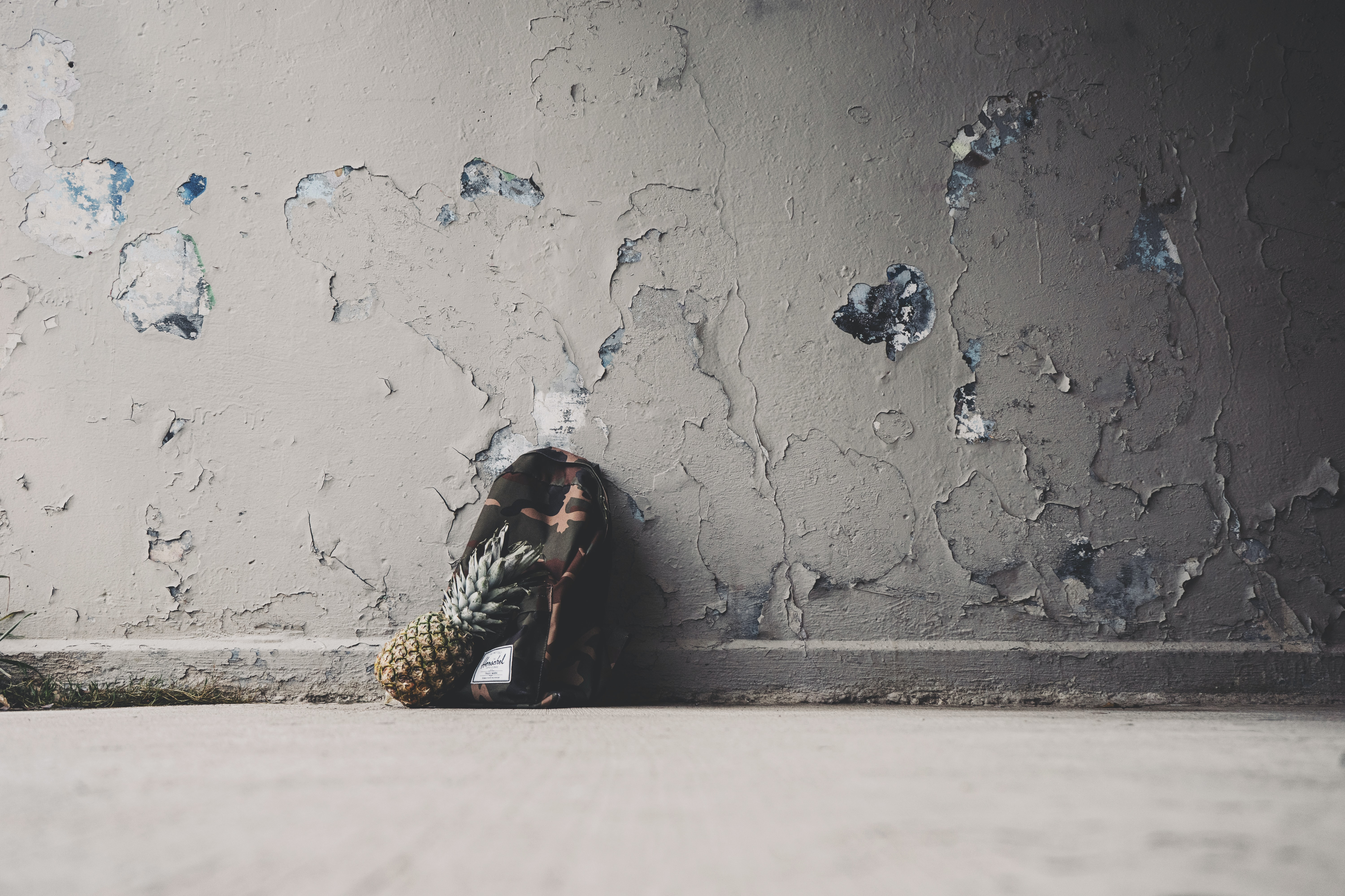 A pineapple and backpack leaning against the wall with chipped paint.
