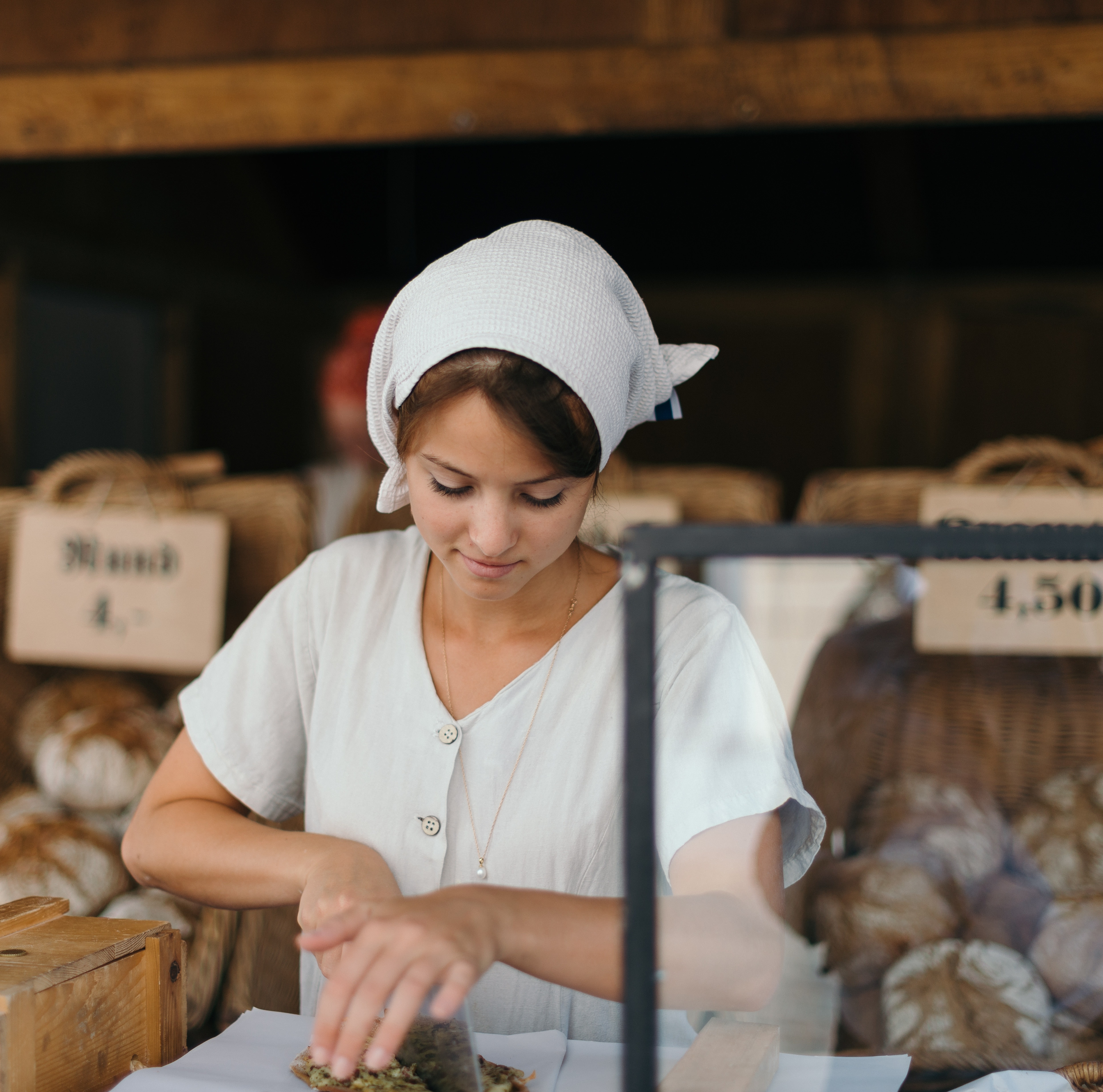 A young woman in a white uniform cutting bread in a bakery