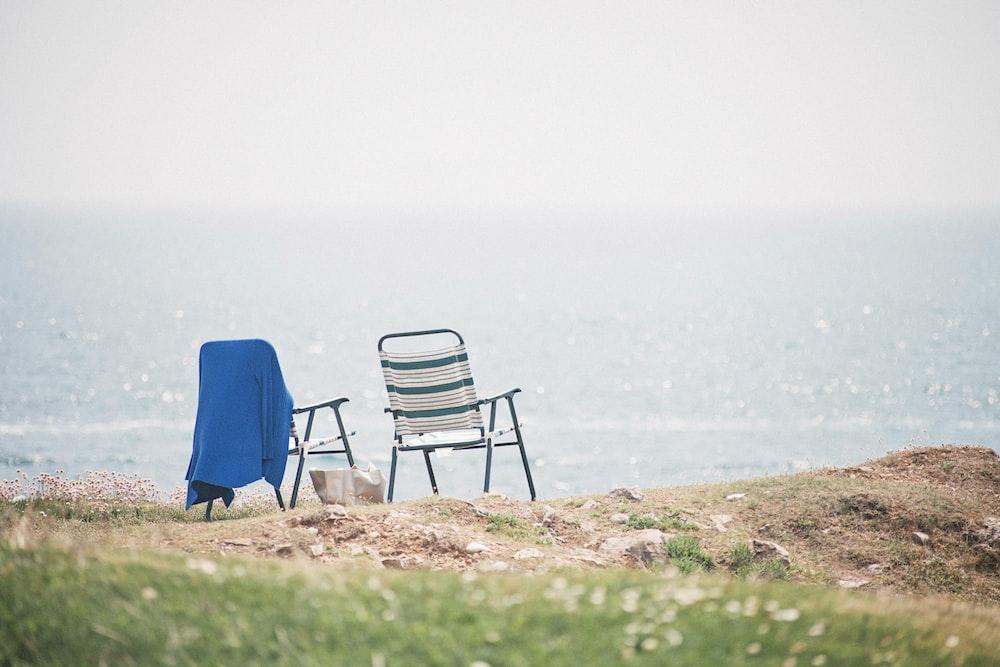 two gray folding armchairs near seashore