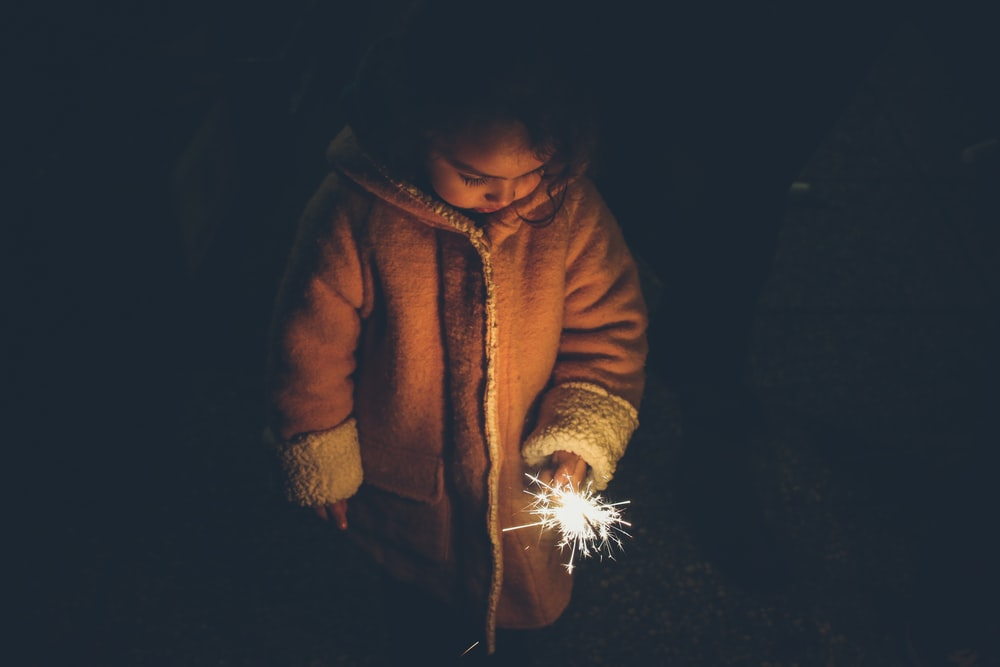 girl holding sparkler at nighttime