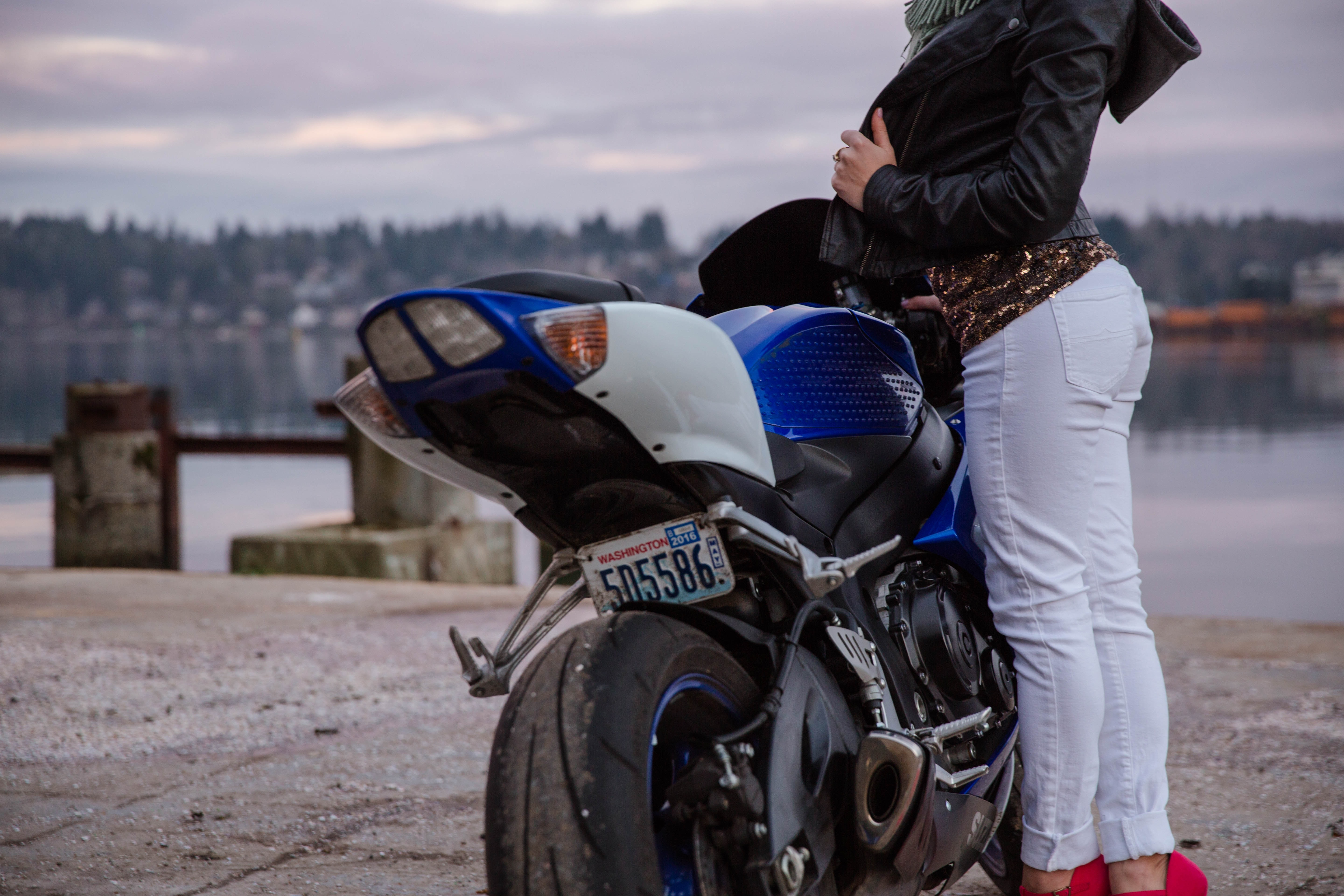 woman standing in front of blue motorcycle