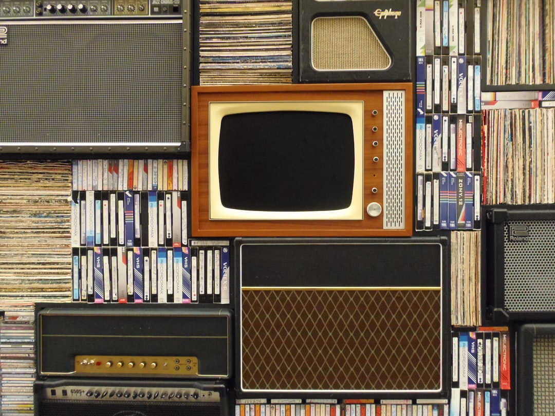 An old television set and several amplifiers among tape cassettes and vinyl records