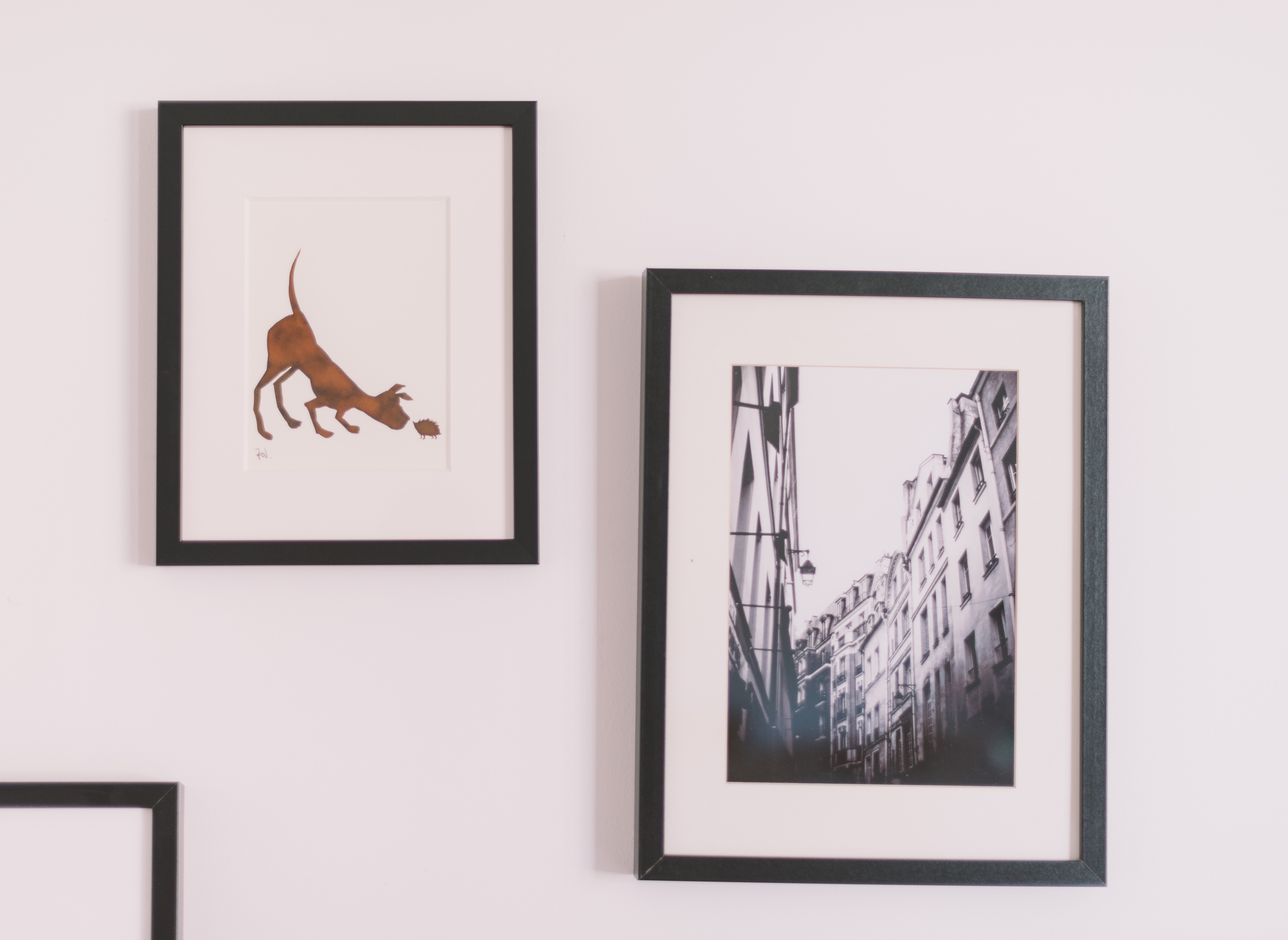 Illustration of dog and black and white photo of urban buildings in frames on white wall