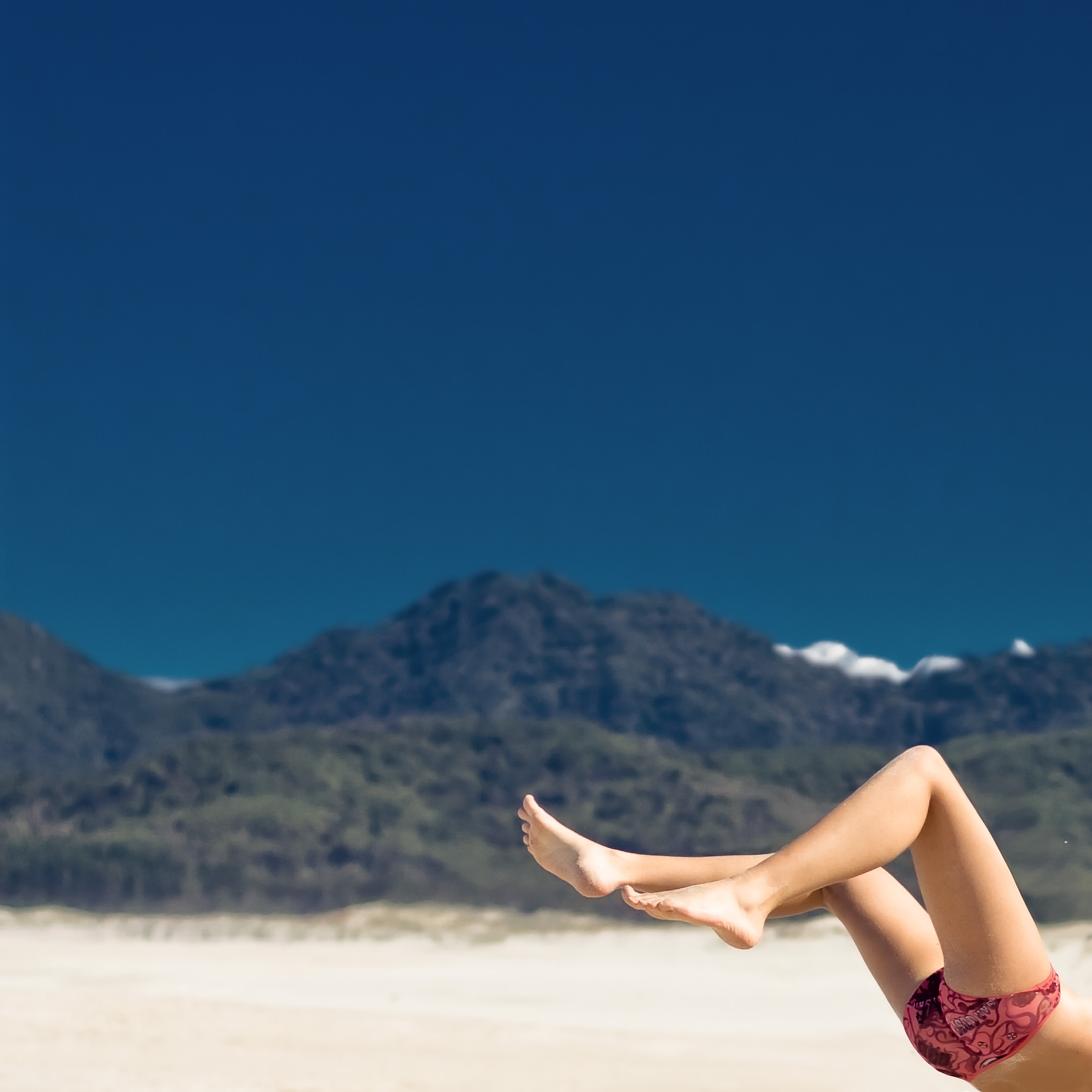 Woman's leg features in landscape view of a huge distant mountain in summer Great Barrier Island