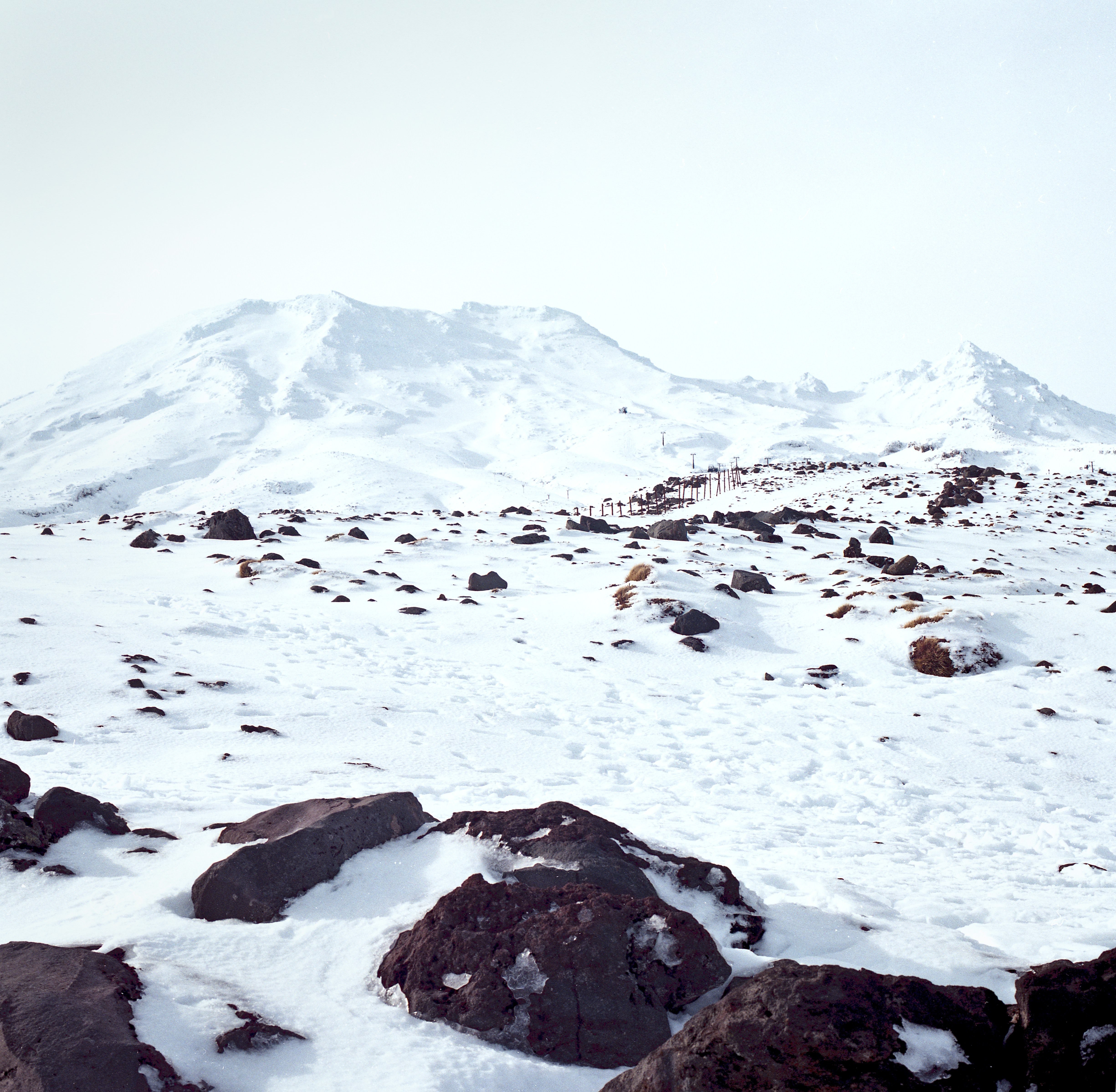 A look up at a peak on a dark brown mountain covered in snow.