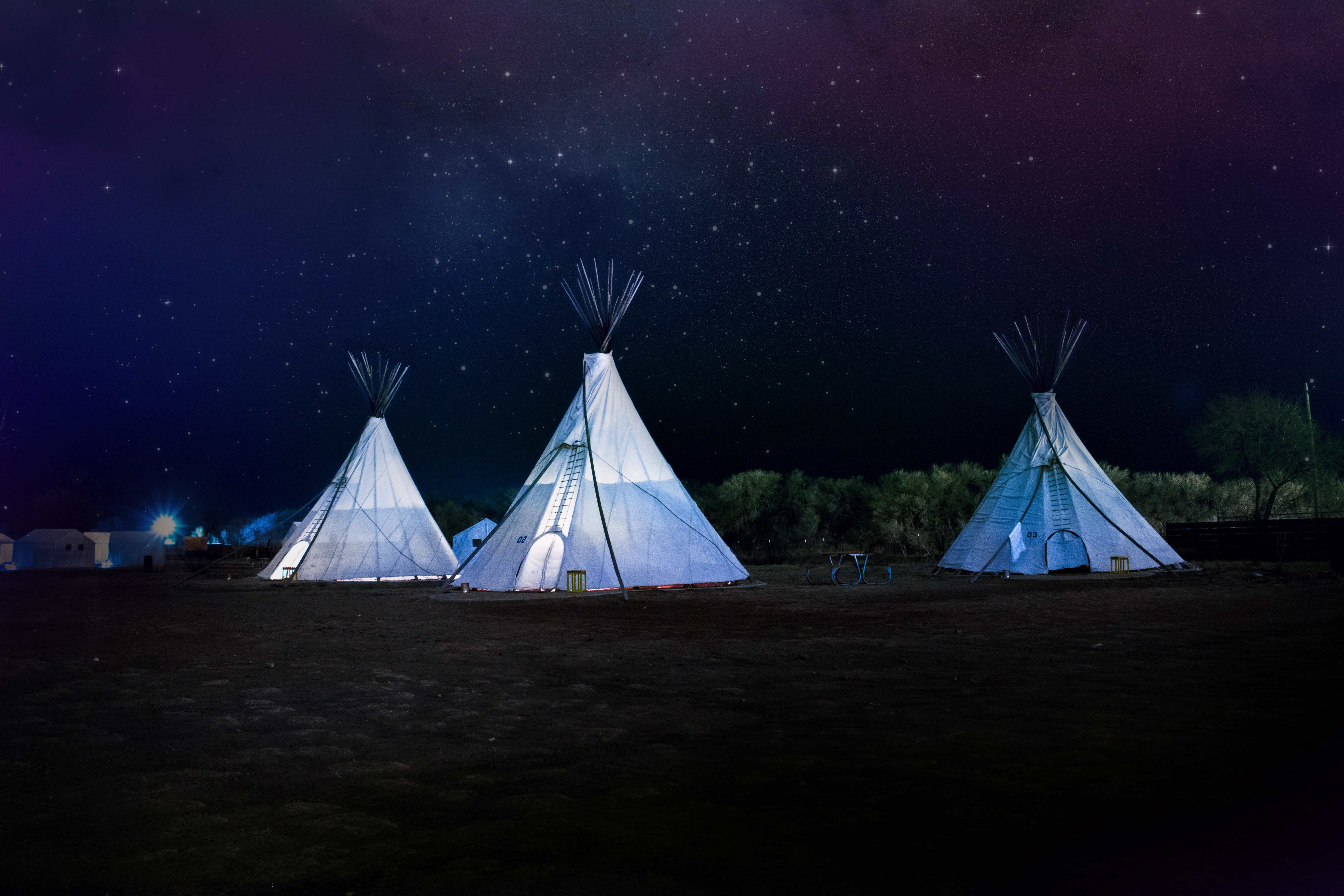 three white teepee tents under starry sky