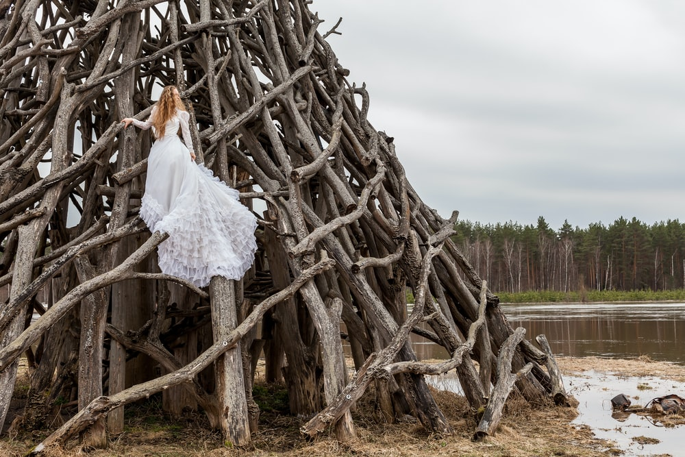 woman in white dress on piled wood logs
