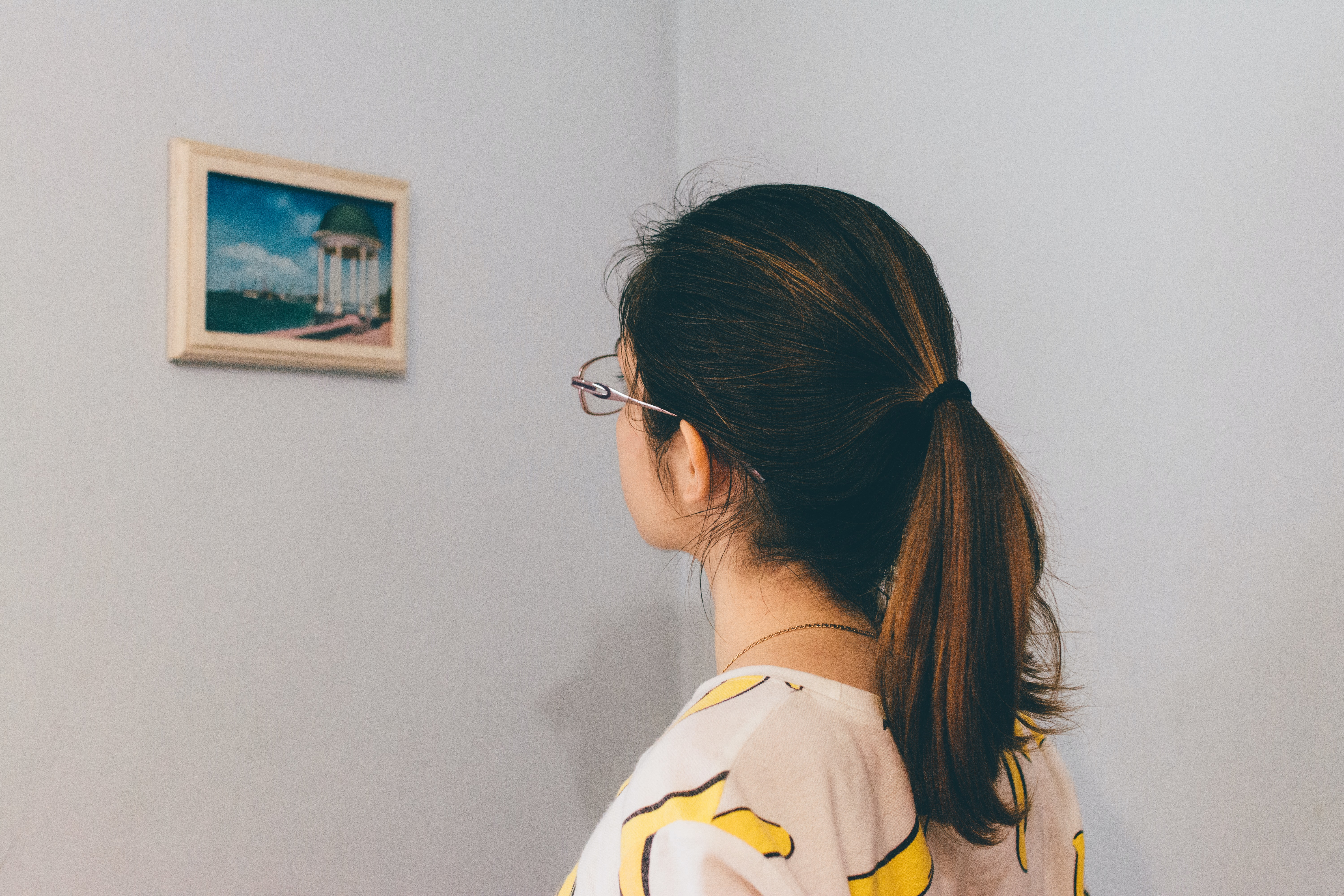 Young woman with glasses from behind looking at small framed artwork on white wall