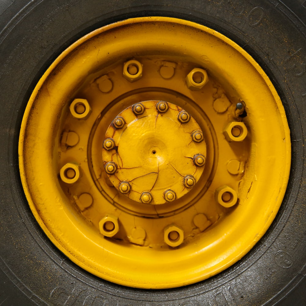 closeup photo of yellow vehicle wheel with tire