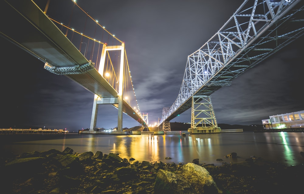 low angle photography of two metal bridges above body of water