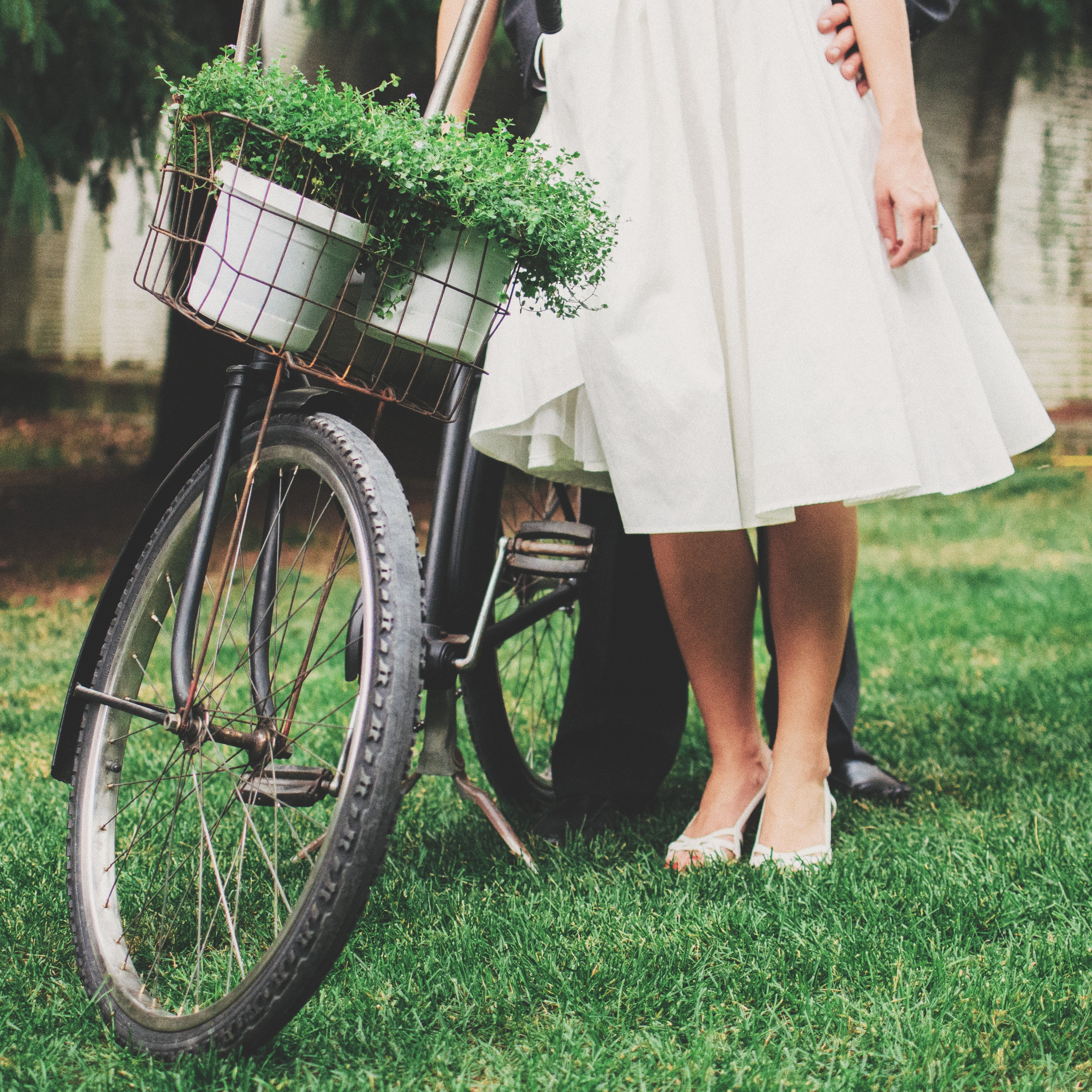 Wedding couple beside bike with a basket of plants on front