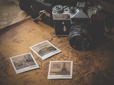 black and grey dslr camera near several photos on brown map vintage zoom background