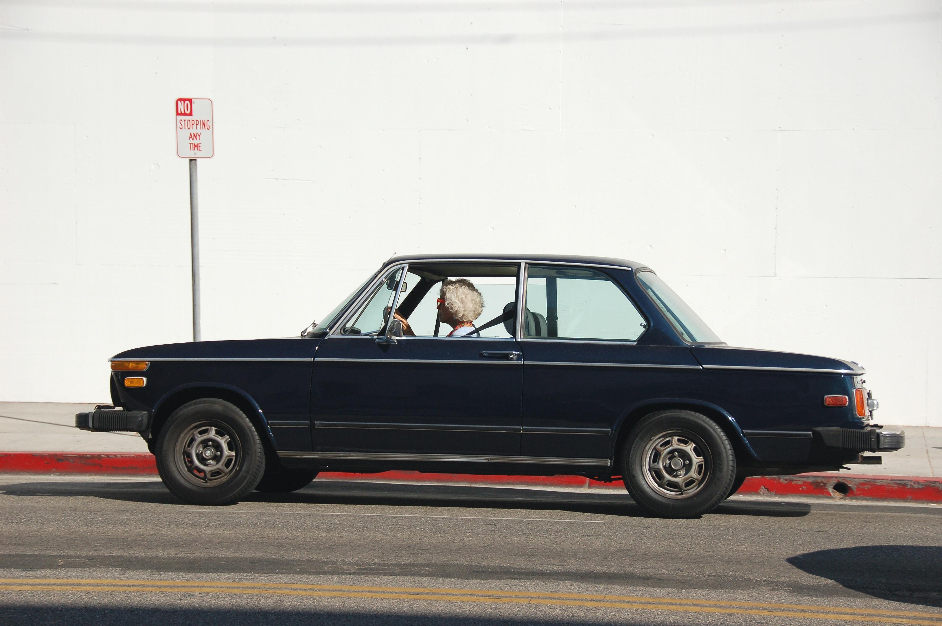 Old woman driving through an empty urban street in a dark blue car, Beverly Hills